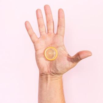 Nahaufnahmemannhand, die ein transparentes kondom hält