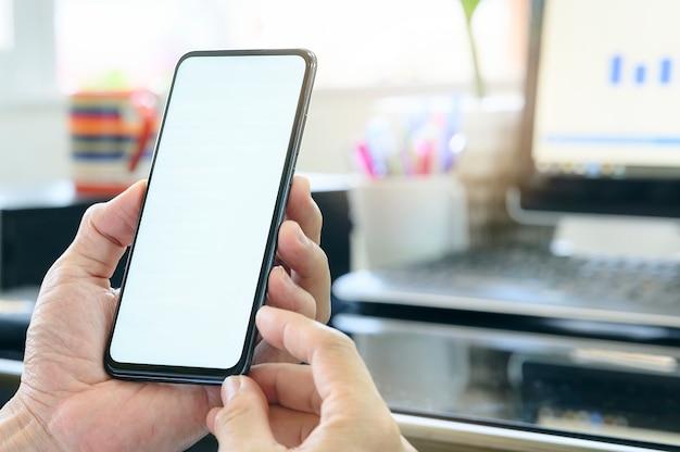 Nahaufnahmemannhand, die smartphone mit leerem weißem bildschirm beim arbeiten am schreibtisch, leerer bildschirm hält