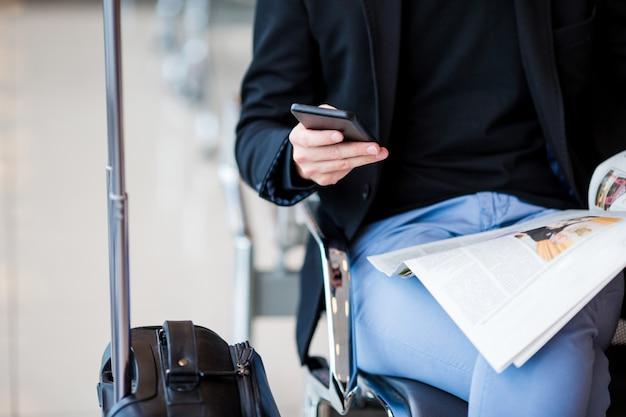 Nahaufnahmemobiltelefon in den männlichen händen am flughafen beim warten auf verschalen.