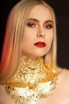 Nahaufnahmemodeporträt der reizenden blonden frau mit roten lippen und goldfolie auf ihrem hals