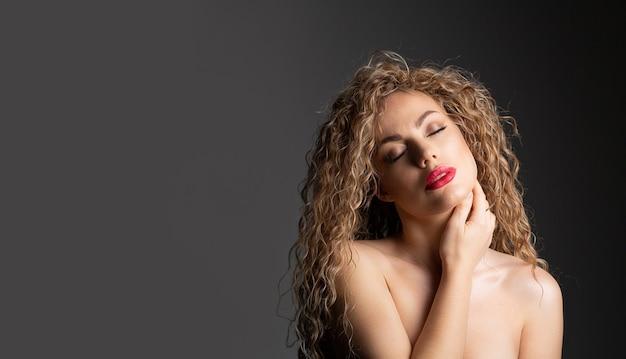 Nahaufnahmemodeporträt einer verführerischen jungen frau mit den roten lippen und dem gelockten haar, das an der grauen wand aufwirft. platz für text