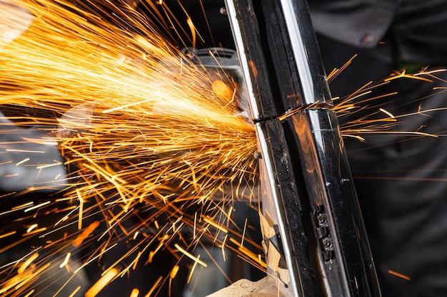 Nahaufnahmen an den seiten fliegen helle funken von der winkelschleifmaschine. ein junger männlicher schweißer mahlt ein metallprodukt mit einem winkelschleifer in der garage