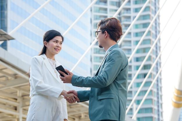 Nahaufnahmen des jungen geschäftsmannes und der asiatischen geschäftsfrau hand in hand. geschäftsleute geben sich die hand