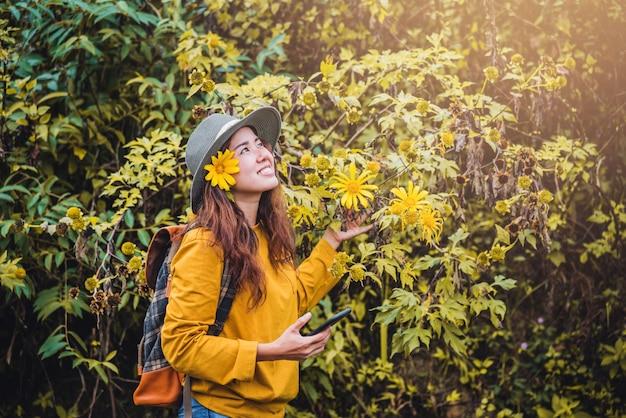 Nahaufnahmen einer glücklichen jungen frau, die die gelbe sonnenblume der schönheit bua tong genießt. tung bua tong in maehongson