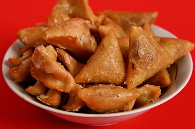 Nahaufnahmen von köstlichen und süßen tellern voller frischer traditioneller luxuriöser marokkanischer handgemachter brewat-süßigkeiten. arabische traditionelle orientalische süßigkeiten auf dem festlichen tisch