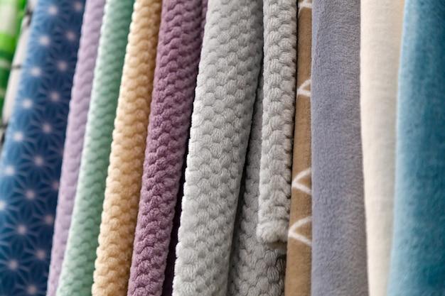 Nahaufnahmen von stoffstücken aus baumwolle, polyester, wandteppich und anderen materialien in verschiedenen farben und drucken zum nähen von vorhängen, bettzeug und kleidung