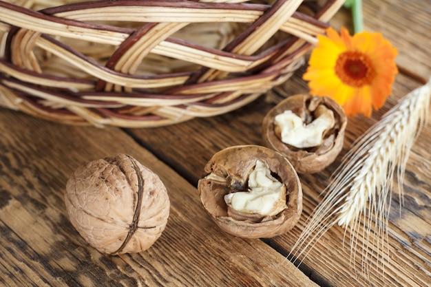 Nahaufnahmen von walnüssen, weizenähren, ringelblumen und weidenkorb auf alten holzbrettern. geringe schärfentiefe. ansicht von oben. Premium Fotos