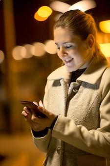 Nahaufnahmenachtporträt der glücklichen frau, die textnachricht auf der straße liest