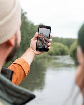 Nahaufnahmepaar, das selfie nahe wasser nimmt