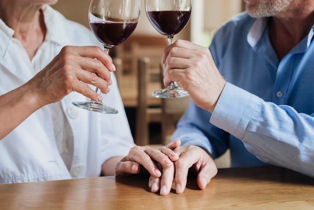 Nahaufnahmepaare, die einen toast am restaurant machen