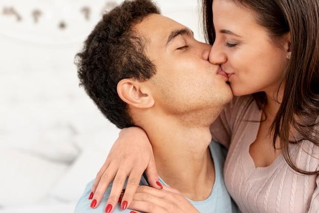 Nahaufnahmepaare, die im schlafzimmer küssen