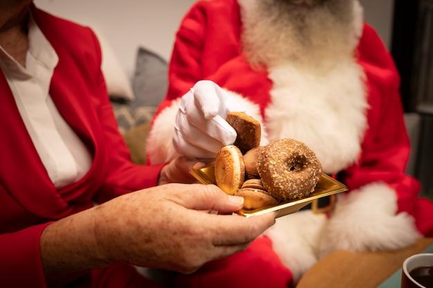 Nahaufnahmepaare, die weihnachtsplätzchen essen
