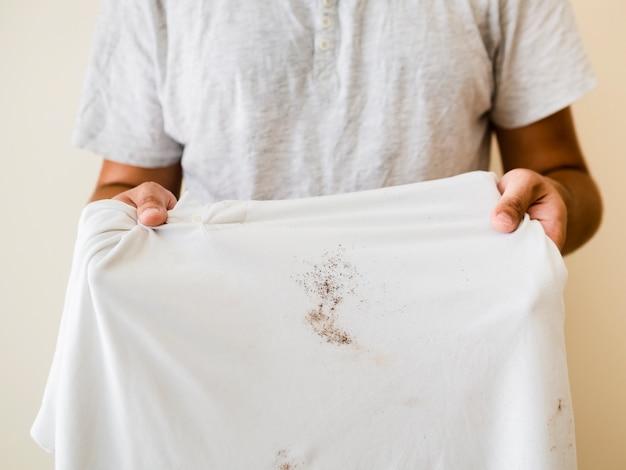 Nahaufnahmeperson, die beflecktes hemd zeigt