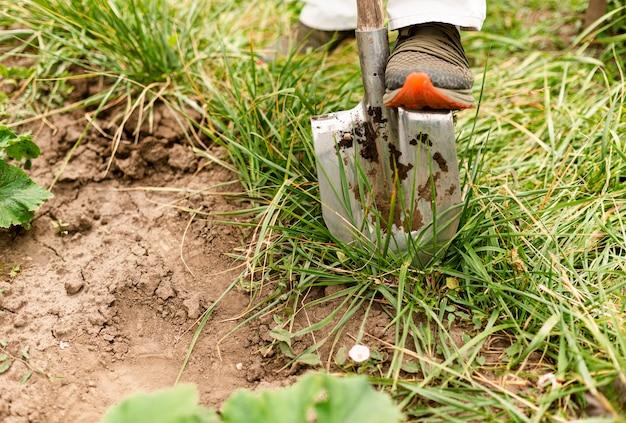 Nahaufnahmeperson, die den garten gräbt