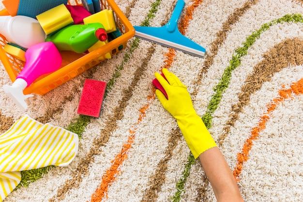 Nahaufnahmeperson, die den teppich säubert