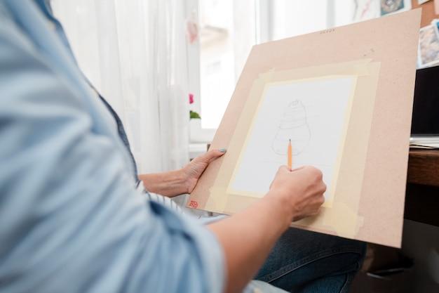 Nahaufnahmeperson, die eine skizze zeichnet