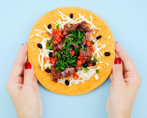 Nahaufnahmeperson, die entfalteten burrito hält