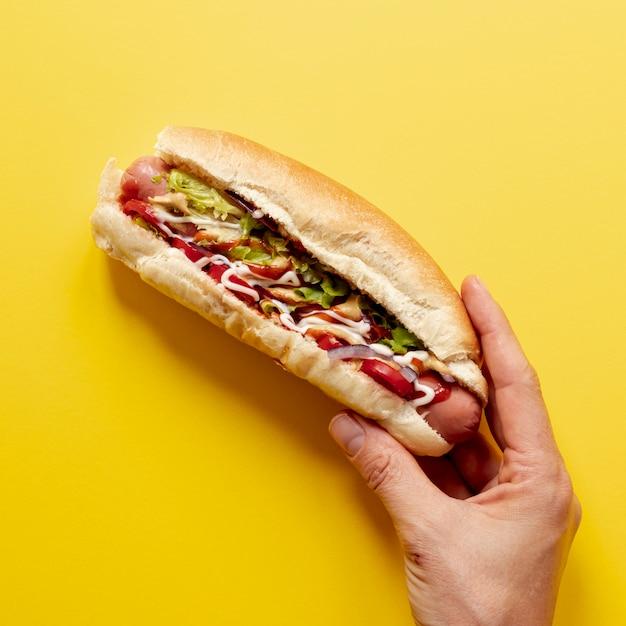 Nahaufnahmeperson, die hotdog hält