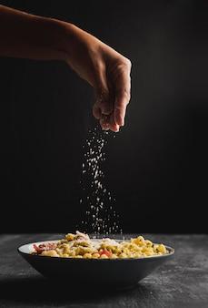 Nahaufnahmeperson, die käse auf teigwaren setzt