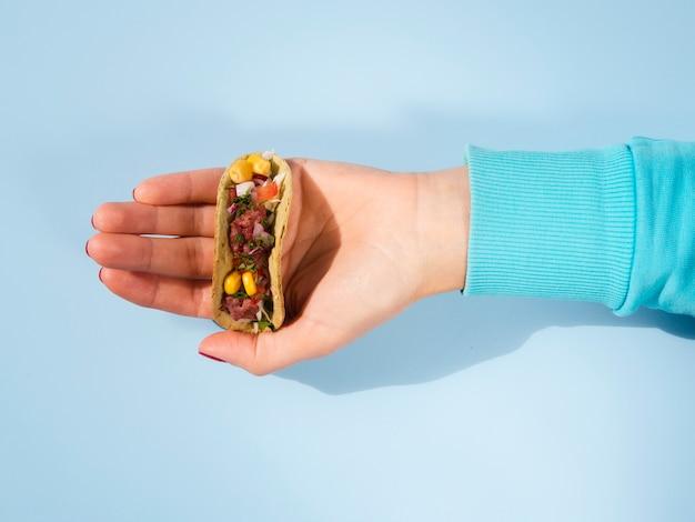 Nahaufnahmeperson, die kleinen taco hält