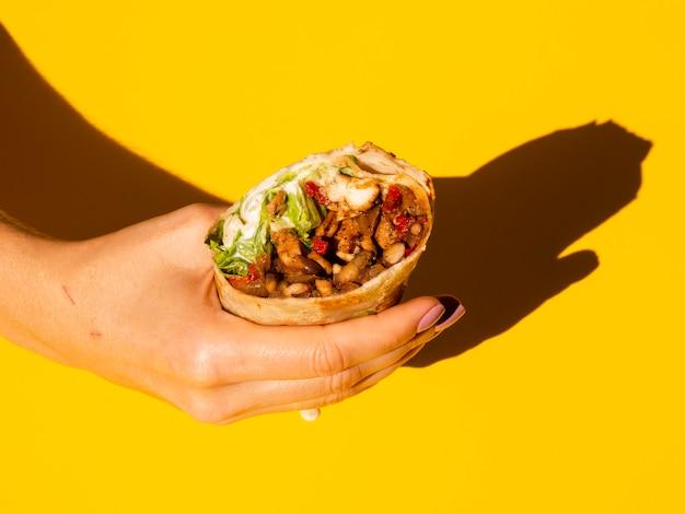 Nahaufnahmeperson, die köstlichen burrito hält