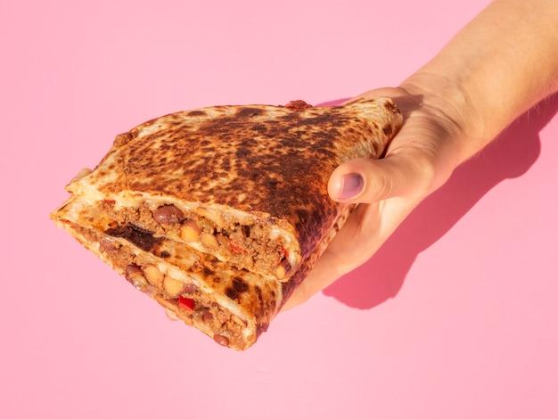 Nahaufnahmeperson, die köstliches mexikanisches lebensmittel hält