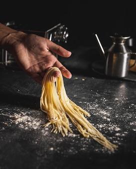 Nahaufnahmeperson, die spaghettis mit einer hand hält