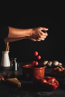 Nahaufnahmeperson, die tomaten in eine schüssel einsetzt