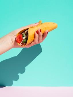 Nahaufnahmeperson mit burrito und blauem hintergrund