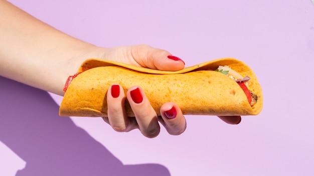 Nahaufnahmeperson mit burrito und purpurrotem hintergrund