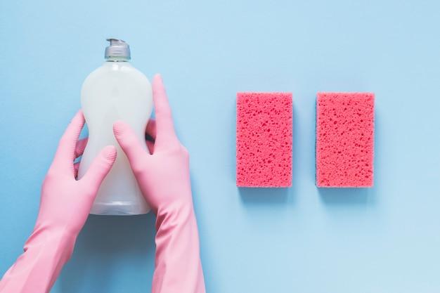 Nahaufnahmeperson mit den handschuhen, die reinigungsmittelflasche halten