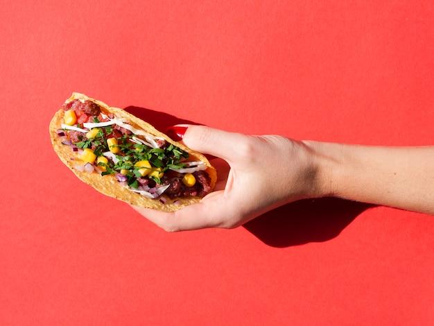 Nahaufnahmeperson mit köstlichem mexikanischem lebensmittel und rotem hintergrund