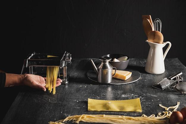 Nahaufnahmeperson mit küchengeräten und dunklem hintergrund