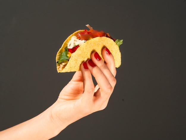 Nahaufnahmeperson mit taco und dunklem hintergrund