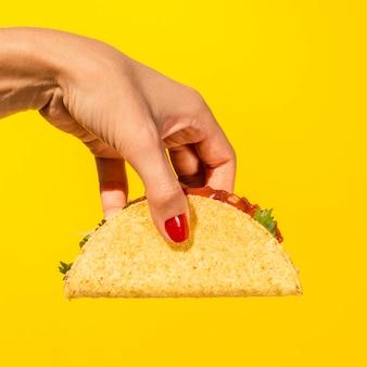 Nahaufnahmeperson mit taco und gelbem hintergrund