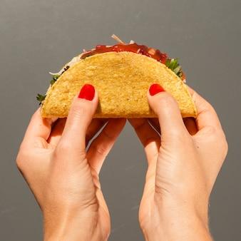 Nahaufnahmeperson mit taco und grauem hintergrund