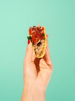 Nahaufnahmeperson mit taco und grünem hintergrund