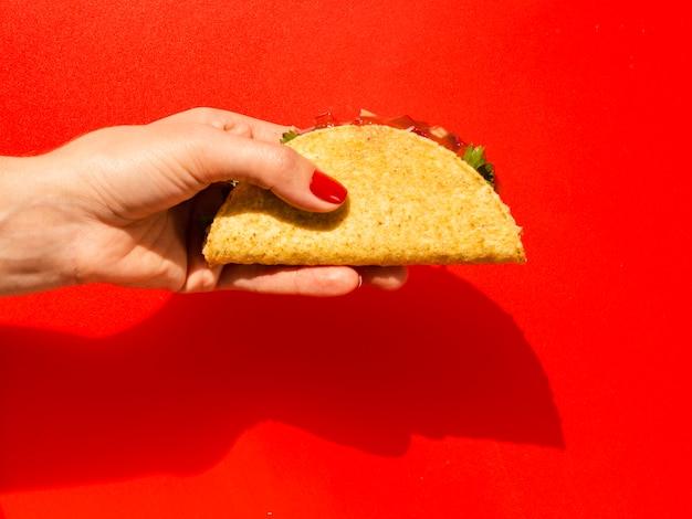 Nahaufnahmeperson mit taco und rotem hintergrund