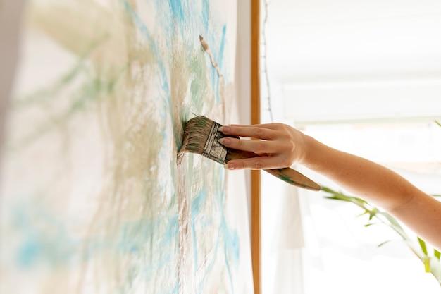 Nahaufnahmeperson, welche die wand malt