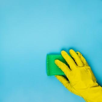 Nahaufnahmepersonenreinigung mit grünem schwamm