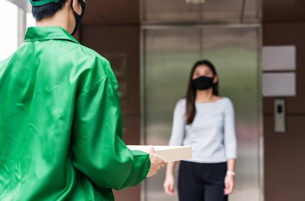 Nahaufnahmepizza-nahrungsmittelbox auf kurierliefermann mit grüner jackenuniform zum weiblichen bürokunden.