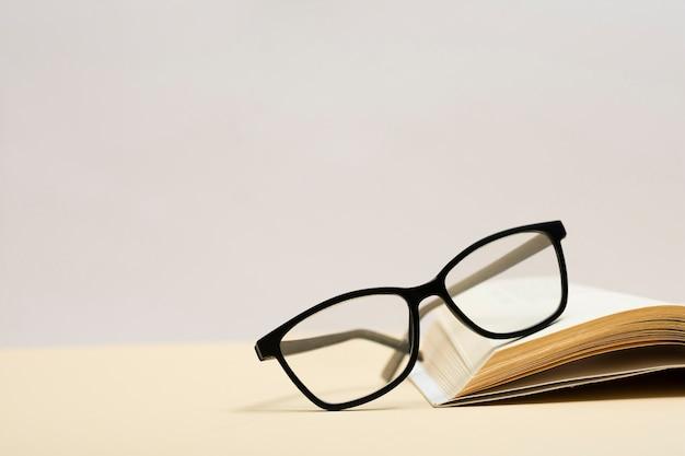 Nahaufnahmeplastikbrillen auf einem buch