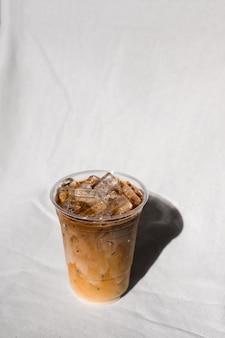 Nahaufnahmeplastikglas eiskaffee mit milch auf dem tisch