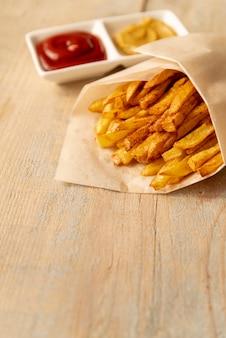 Nahaufnahmepommes-frites mit hölzernem hintergrund