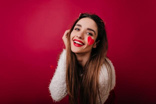 Nahaufnahmeporträt der anmutigen dame mit dunklem haar, das am valentinstag herumalbert