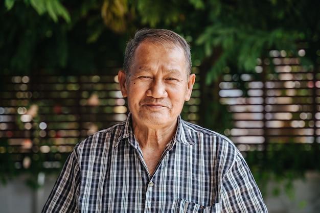 Nahaufnahmeporträt der asiatischen älteren mannaufstellung des lächelns. alter thailändischer mann