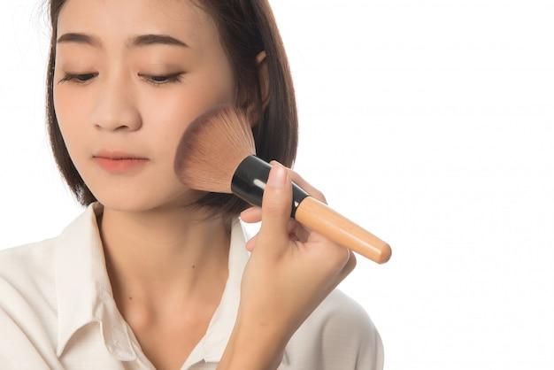 Nahaufnahmeporträt der asiatischen frau schoss haar, das trockenes kosmetisches tonales fundament auf ihrem gesicht unter verwendung des make-up-pinsels auf weiß anwendet