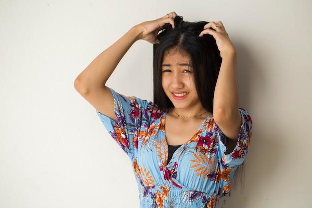 Nahaufnahmeporträt der asiatischen jungen frau, die kopf mit hand kratzt