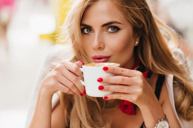 Nahaufnahmeporträt der atemberaubenden blauäugigen dame, die im café kühlt und heißen kaffee trinkt