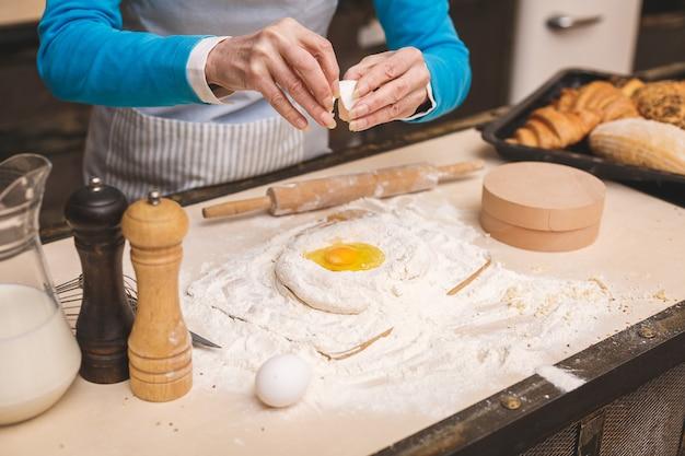 Nahaufnahmeporträt der attraktiven älteren gealterten frau kocht auf küche. großmutter macht leckeres backen.